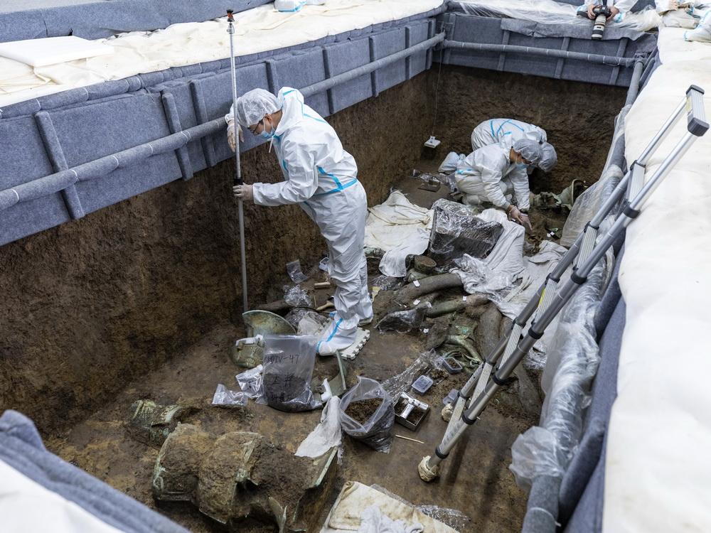 """在三星堆遗址考古发掘现场3号""""祭祀坑"""",考古人员用全站仪为新发现的文物定位(3月10日摄)。 新华社记者 沈伯韩 摄"""