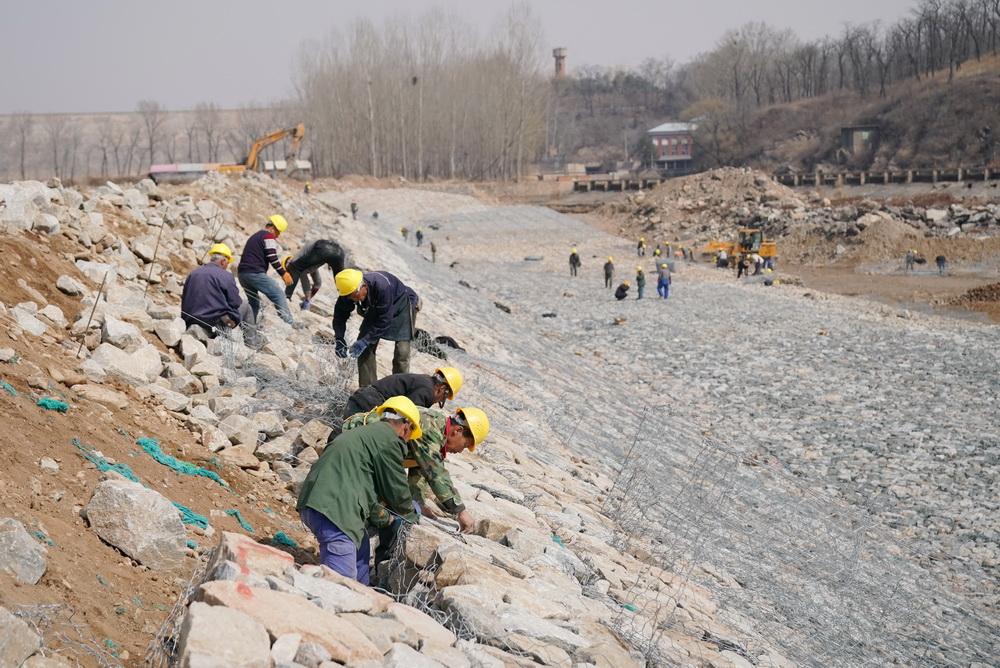 3月23日,工人在秦皇岛市洋河水库除险加固工程泄洪道改扩建工地施工。