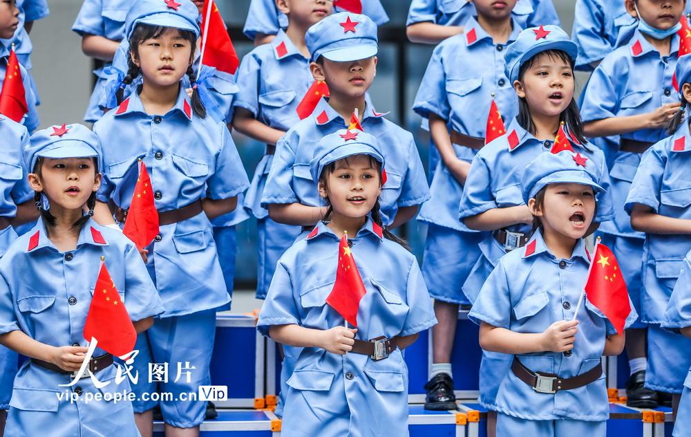 5月31日,南宁市滨湖路小学长虹校区的学生们挥舞国旗,唱响红色歌曲。