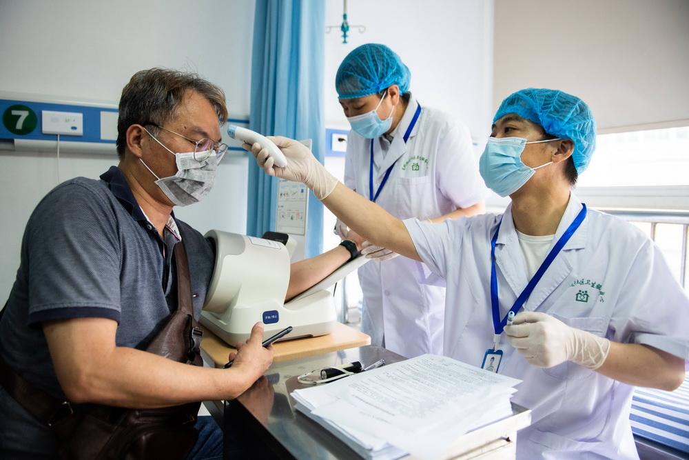 6月12日,在长沙市高桥街道社区卫生服务中心,一名台胞在接种前测量体温。