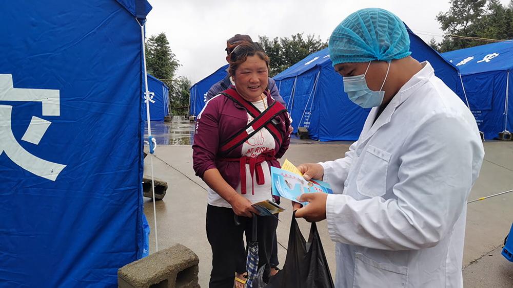 6月13日,在盈江县卡场镇卡场村委会咱巴石村村民小组地震救灾安置点,工作人员向村民宣传传染病防控知识。