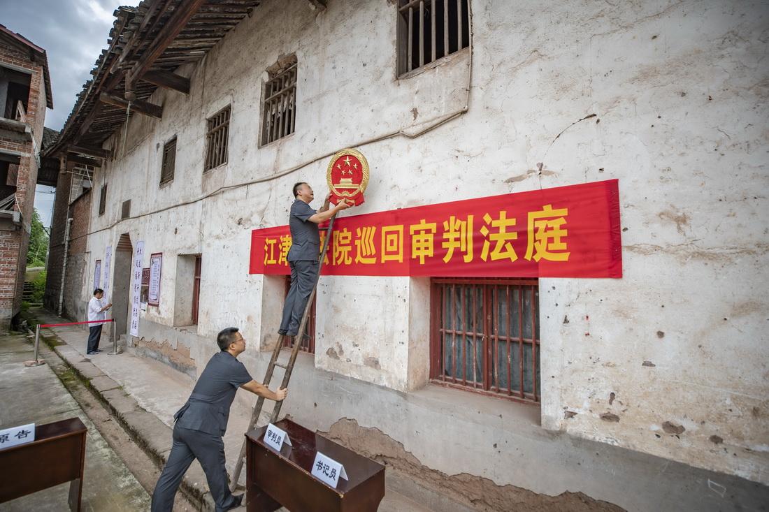 9月17日,在重庆市江津区蔡家镇文昌村塘口村民小组,重庆市江津区人民法院第二人民法庭法官徐驰(上)和同事李瑞鑫在设置巡回审判法庭。