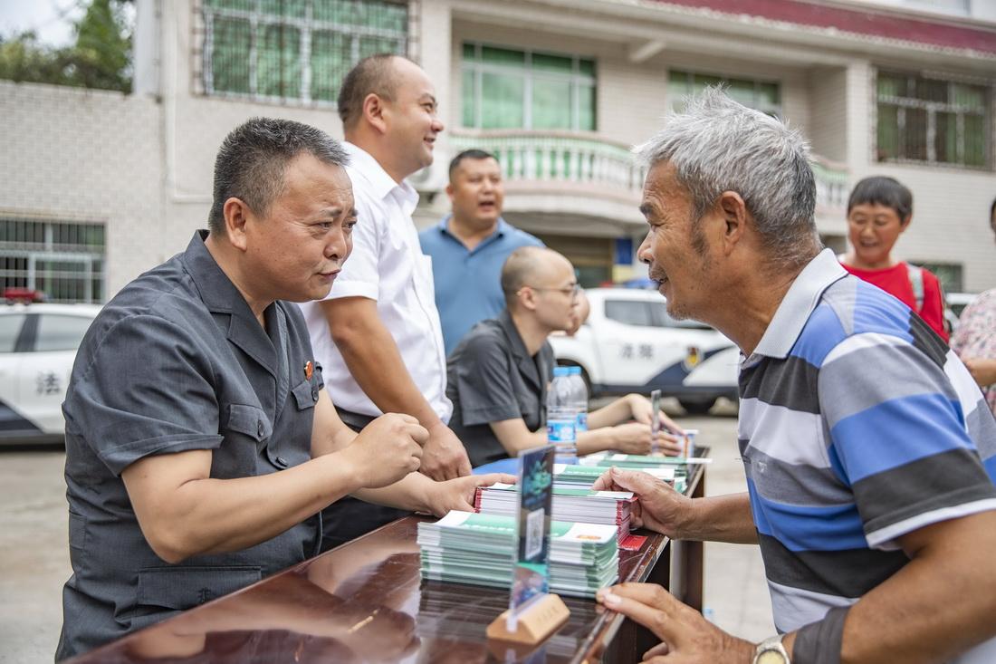 9月17日,在重庆市江津区蔡家镇鸳鸯村,重庆市江津区人民法院第二人民法庭法官徐驰(左一)与前来进行法律咨询的村民交谈。