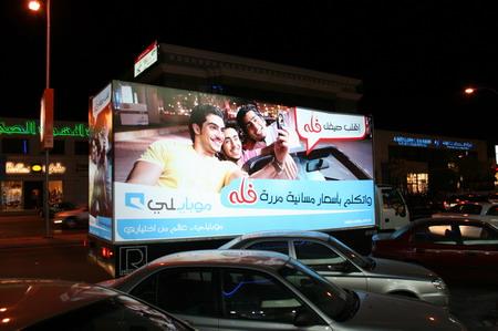 一辆载着大型灯箱广告的汽车在街头行驶.-沙特街头的汽车灯箱广告图片