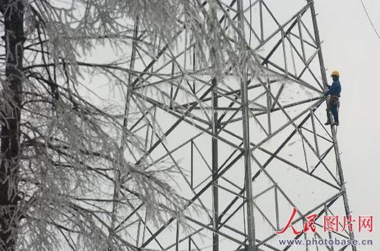 电力抢修人员在高压线塔上除冰
