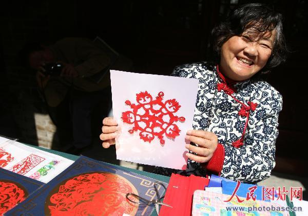 3月27日,在江苏镇江市古城西津渡街一位民间剪纸艺人在展示剪纸艺术
