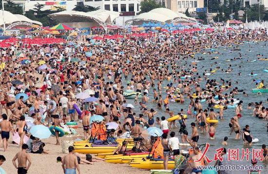 在青岛第一海水浴场,海滩上挤满了前来游泳的游客和市民.