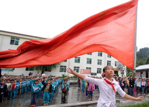 隅镇中心小学的小学生们在举行升旗仪式-边境线上的欢乐小学