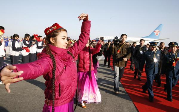 12月16日,维吾尔族姑娘在哈密机场用舞蹈迎接首航班机的到来.