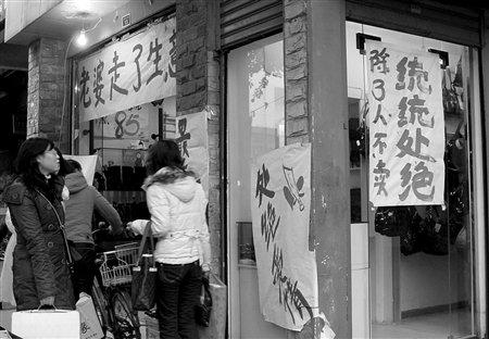 纱毂行街边一女性服装店贴出五花八门的促销广告语图片