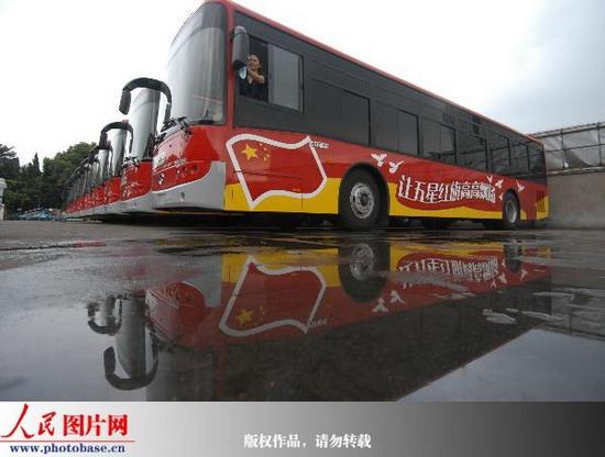 人民网讯 2009年8月31日,喷绘有五星红旗图案的公交车在宁波公交总公司亮相,并将投入运营。为迎接国庆60周年,宁波市公交总公司在60辆全新公交车上喷绘让五星红旗高高飘扬主题彩色图案,将成为市区一道亮丽的风景线。 据了解,其中41辆公交车为刚引进的新车,两边装有推拉隐私玻璃,能够有效的遮挡烈日。