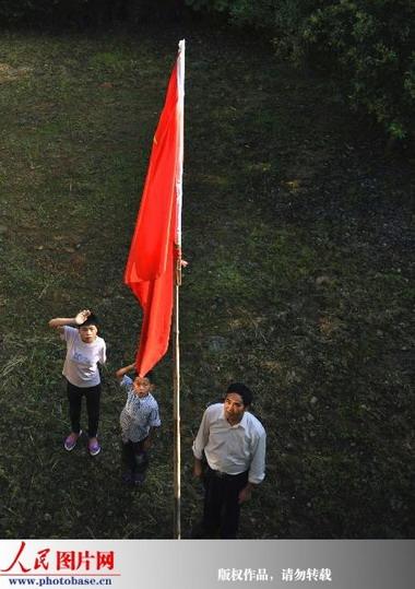 )在升旗仪式上向国旗敬礼. 版权作品,请勿转载.-五星红旗高高