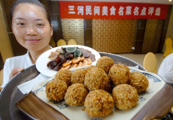 服务员正在展示三河特色民间菜肴糯米圆子(