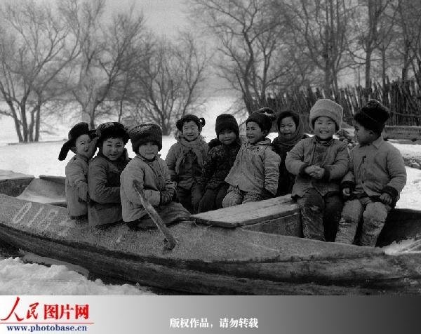群同龄的赫哲族儿童在渔船上合影,1987年.陈涤 摄 版权作品,请
