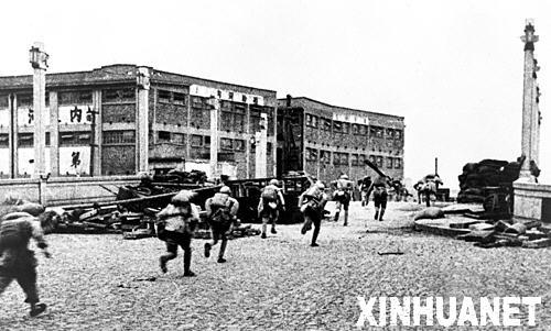 海战役中,中国人民解放军战士冲过上海市苏州河上的船板厂,迂回
