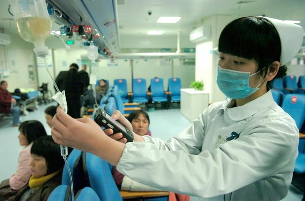 护士正在用随身携带的掌上电脑核对病人的输液药剂