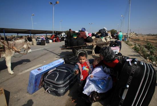 加沙地带的巴勒斯坦人在通往埃及的拉法口岸外排队等待过境.-巴勒