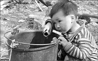 在贵州省兴义市郑屯镇绒窝村王家凼组,一名小男孩拿着水管蹲在水桶旁