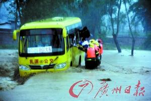 客车在激流中载沉载浮,救援人员抢救车上乘客。 卜瑜 摄