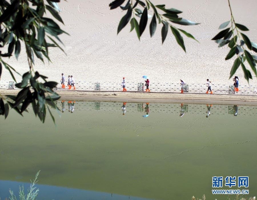 7月16日,游人在风景秀美的敦煌月牙泉畔赏景。