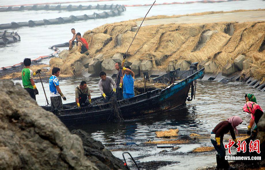 7月30日,清污人在大连泊石湾海滨浴场清理污染物,由於大量的原油泄漏