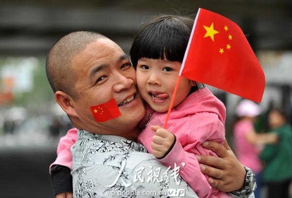 上海 世博会/小女孩手拿五星红旗和她脸上贴着国旗的父亲在园区内留影。