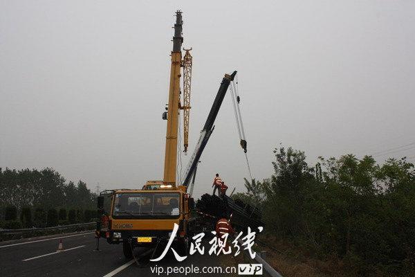 2010年10月18日下午,两辆吊车将翻出高速公路的大卡车吊起。