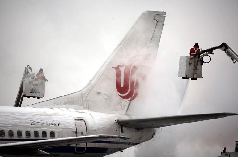 2月13日,北京首都国际机场的工作人员在为飞机除冰.