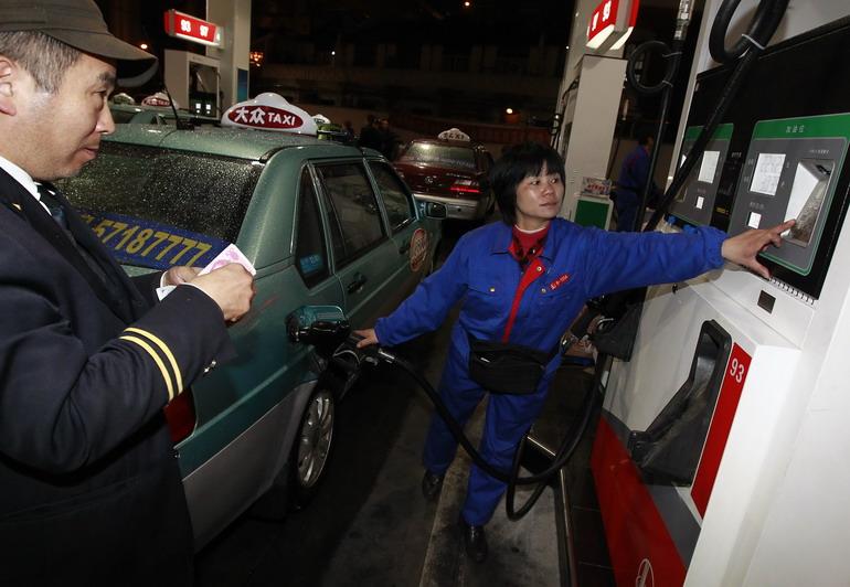 月7日零时许,上海一位出租车司机(左)正在加油站内为车辆加油